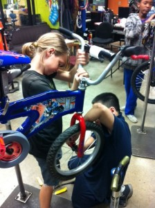 Ellis and See work on a bike at Cycles for Change
