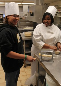 LaMerria rolls out the pasta dough at with a culinary arts student at St Paul College.