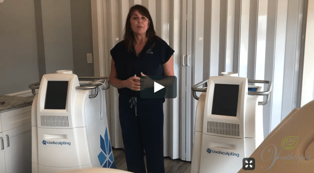 Owner #1 Med Spa Alpharetta is wearing black scrubs and talking about coolsculpting while standing next to a coolsculpting machine