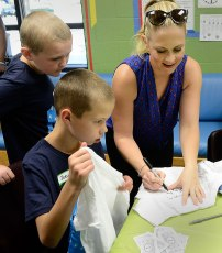 Hart signs t-shirts during her visit.