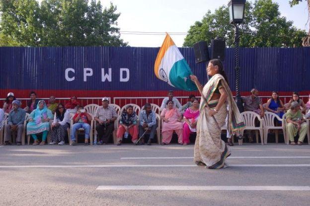 Une femme indienne avec un drapeau indien le long de la frontiere pakistanaise à Amristar en Inde photo blog voyage tour du monde https://yoytourdumonde.fr