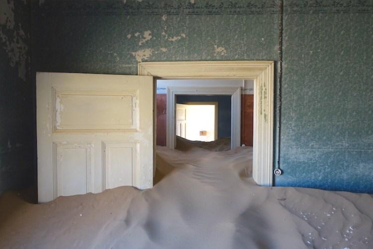 Désert Namibie qui monte jusqu'au toit des maisons de Kolmanskop ville fantôme en Namibie photo blog voyage tour du monde travel https://yoytourdumonde.fr