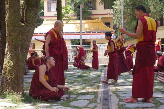 Des jeunes moines bouddhistes débattent en se tappant la main du coté de Dharamsala en Inde photo blog voyage tour du monde https://yoytourdumonde.fr