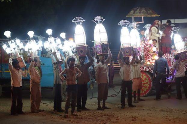 Lors d'un mariage à Agra en Inde des hommes portaient des lumières photo blog voyage tour du monde https://yoytourdumonde.fr