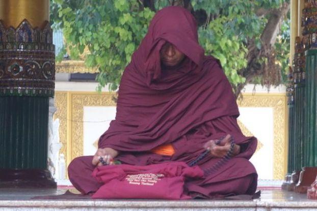 Un moine bouddhiste entrain de mediter dans La Pagode Shwedagon il ressemble cependant un a acteur de star wars photo blog tour du monde https://yoytourdumonde.fr