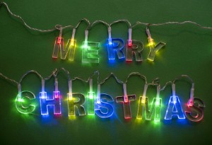 Close-up of lighted Merry Christmas garland on green background