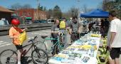 """""""Opening Day for Trails"""" drew crowds of cyclists and walkers last Saturday, the bluest of a blue string of spring days. Brian Housh, right, Midwest policy manager for Rails-to-Trails, staffed the information table in front of the Yellow Springs train station, where cyclists stopped for trail brochures, maps, faux """"tattoos,"""" t-shirts and more. (Photo by Audrey Hackett)"""