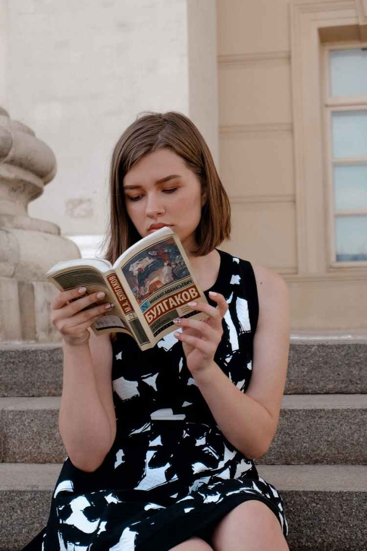 charming woman reading book on steps