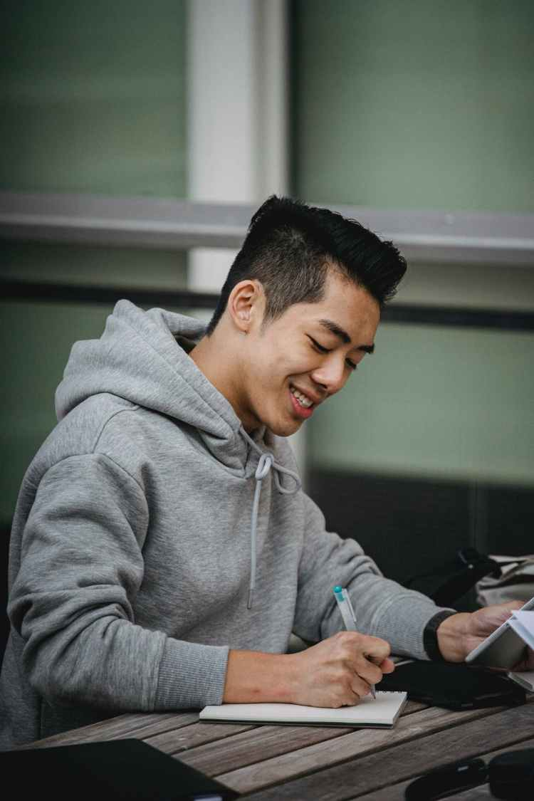 cheerful ethnic man writing in notebook