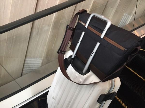 穿過行李箱提把的樣子及背面的拉鍊夾層