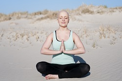 Young beautiful doing yoga on the beach after enduring chemotherapy because of cancer. Sport is most important to get through the rough therapy and to face a positive and healthy future.