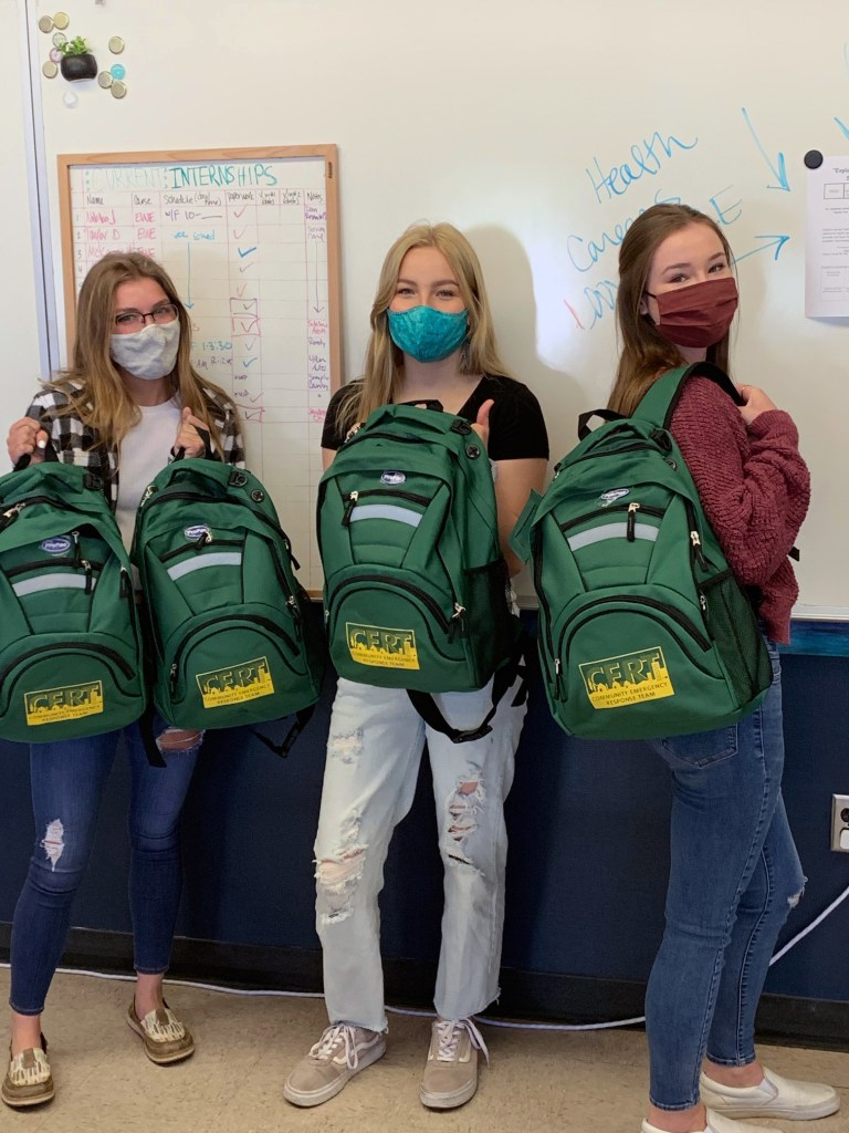 High school students holding supply bags that each student will receive at the completion of the CERT training.