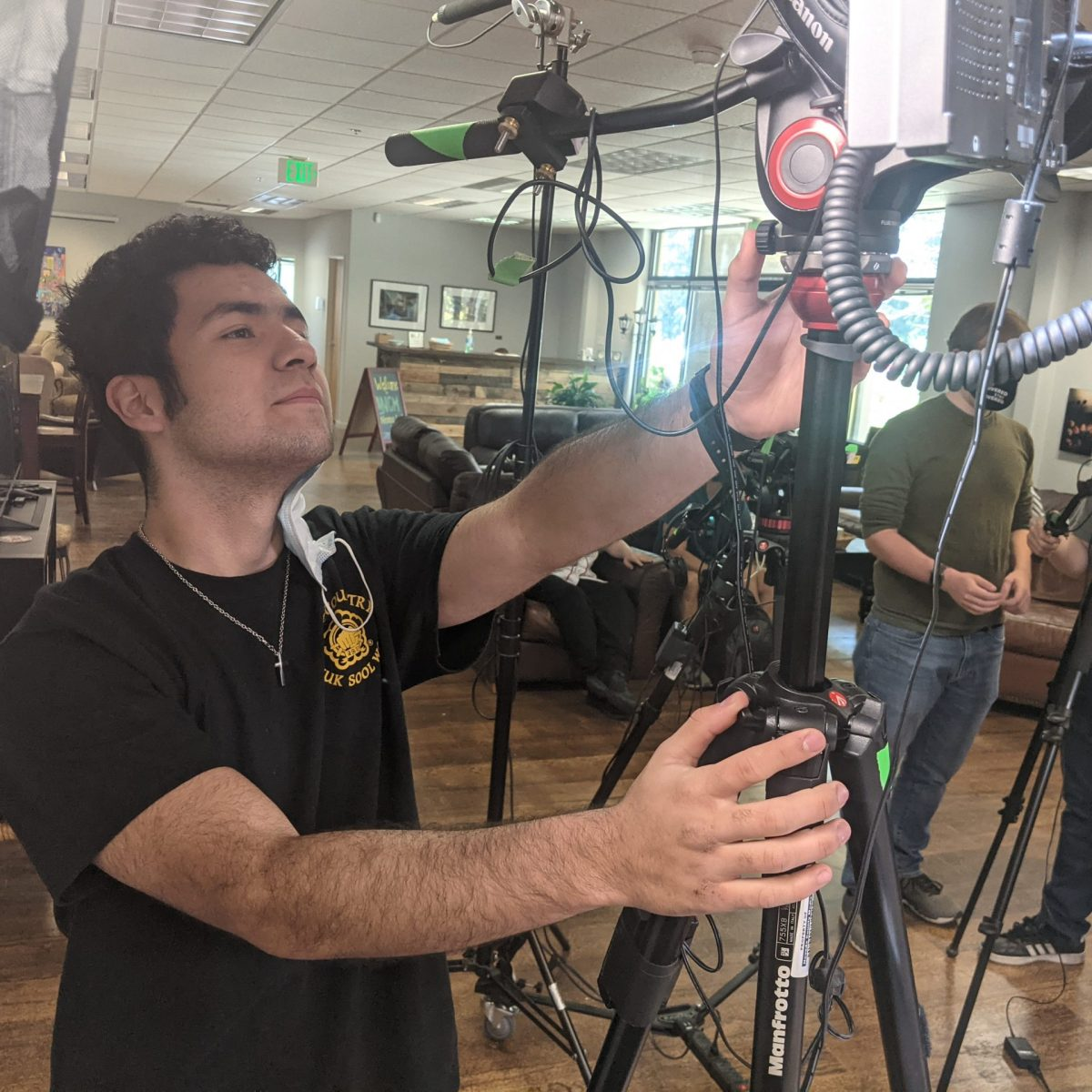 """Nevada County Media intern Xavier Barnhart adjusts a video camera during the recent filming of the monthly local show, """"Let's Get Cooking,"""" at NCM's new studios in the Whispering Pines industrial park in Grass Valley. Also in the studio are Production Manager Andrew Rolland, center, and intern Tal Vinizky, right."""