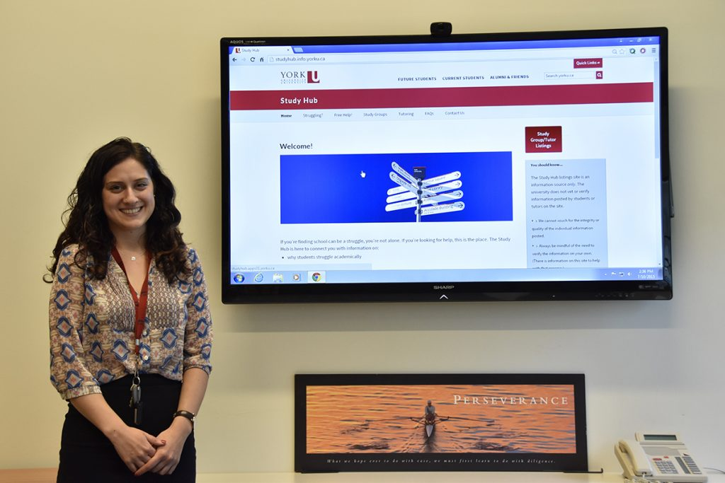 Woman standing to the side of a TV monitor with the Study Hub webpage on screen.