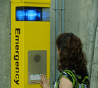 A student uses a Blue Light Safety Phone on campus