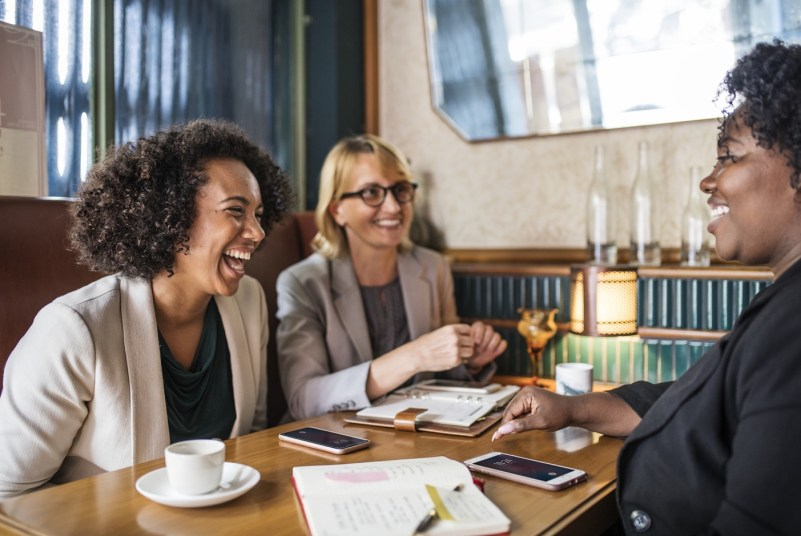 An image of three women at a cafe talking and laughing.
