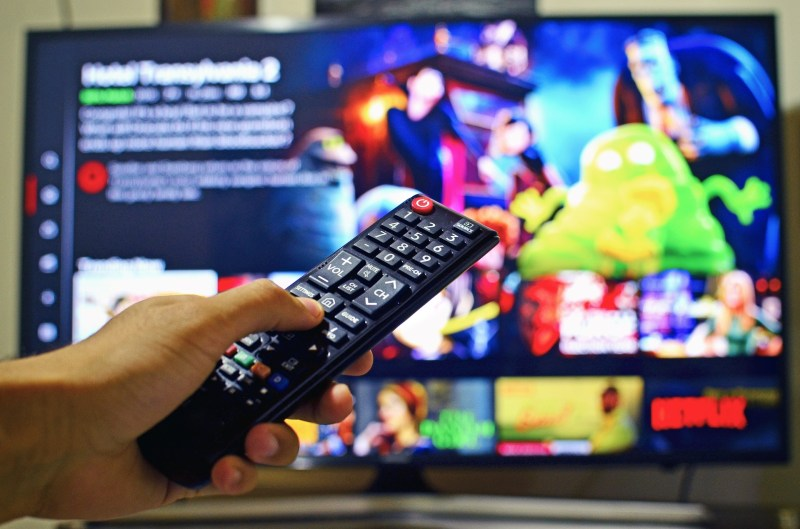 A photo of a person selecting a movie on Netflix, with a focus on the remote control.