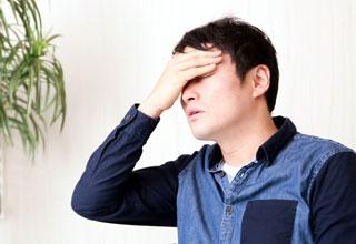 頭痛で頭を押さえる男性