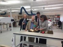 Zyats looks at the Voynich with guests in the Gates Conservation Laboratory