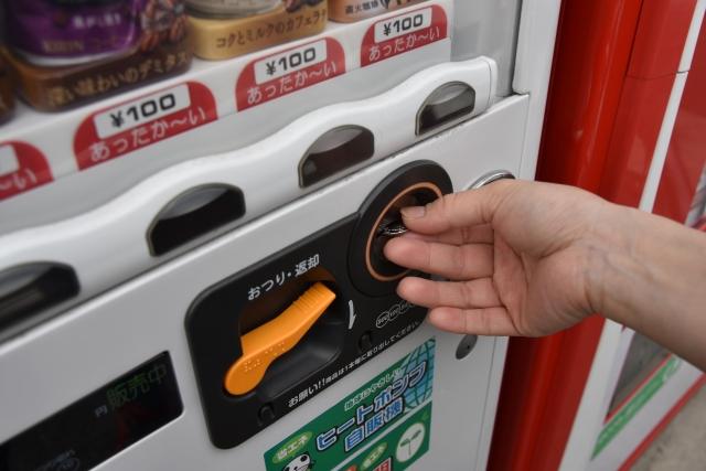 自動販売機でジュースを買う