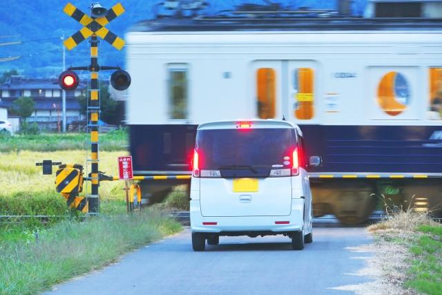 踏切の前で電車が通過するのを待つ