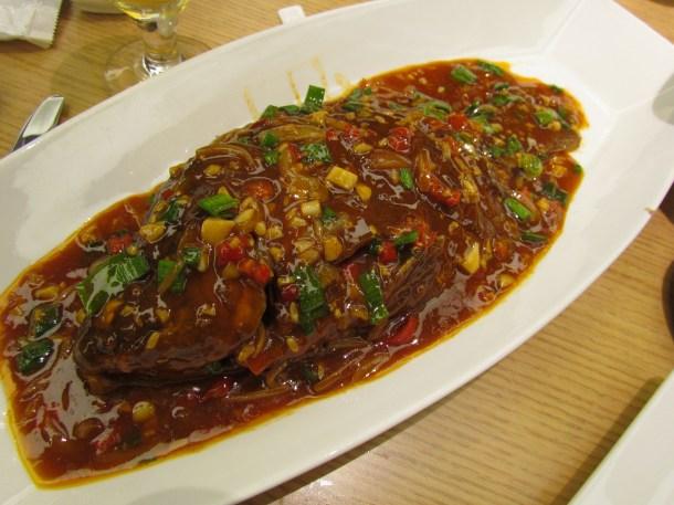 Full fish with garlic chunks, chillies & onion plant