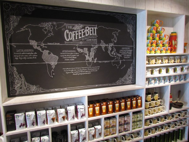 A chalk on blackboard Coffee map of the world + merchandize all around - Coffee beans, cups, powdered coffee etc.
