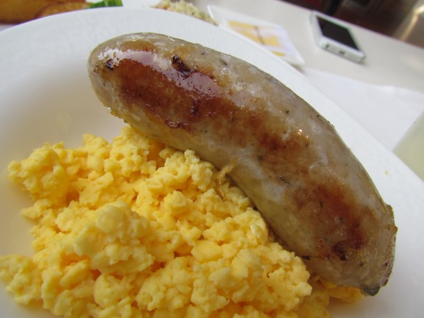sausage atop scrambled eggs