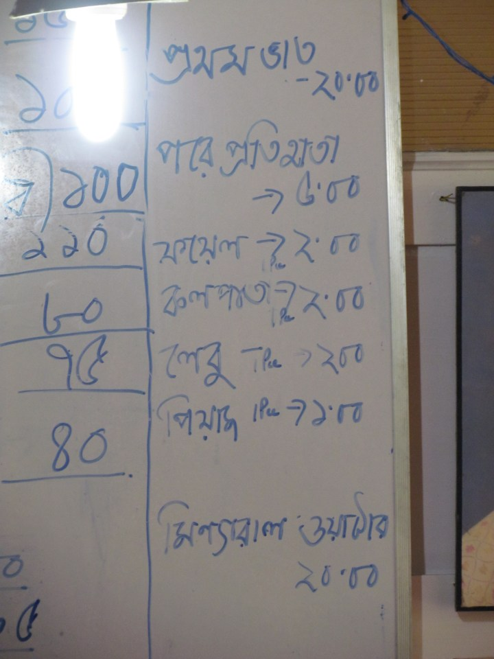 A white board showing rates to be charged for lemon, banana leaf etc