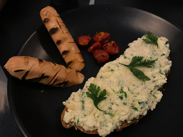 Scrambled egg with garlic, parsley, Parmesan on toast, thyme roasted tomatoes and grilled chicken sausage