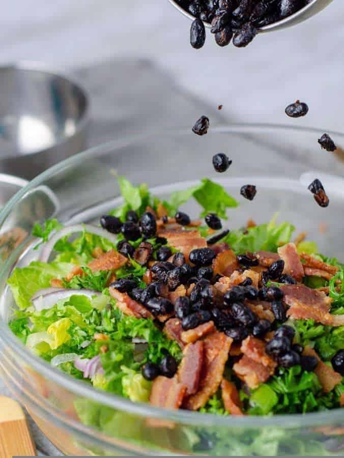 Keto fried black beans sprinkled on a a caesar salad
