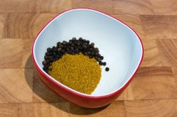 Clive of India curry powder and dried whole black peppercorns