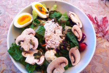 Green salad on plate with eggs and blue cheese dressing