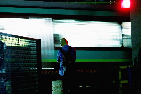 電車通過を待つ人