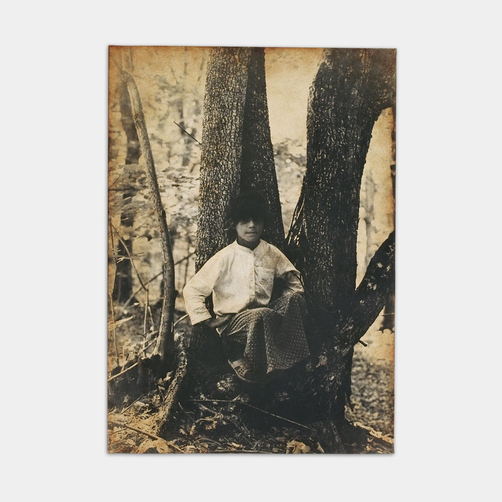 森の中で座るジプシーの少女の写真(正面)