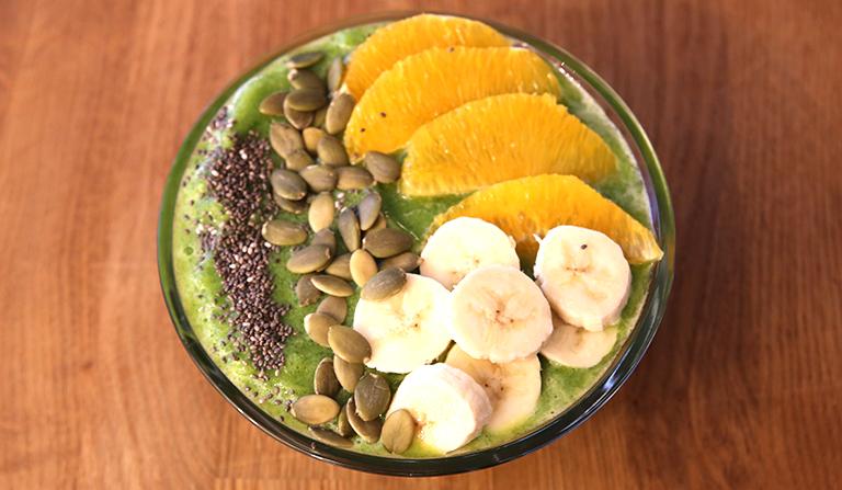 Glassbolle med smoothie, med frukt og frø på toppen.