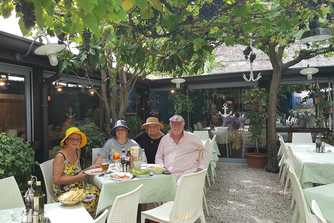 Living and traveling with cancer. Italy - dining with friends.