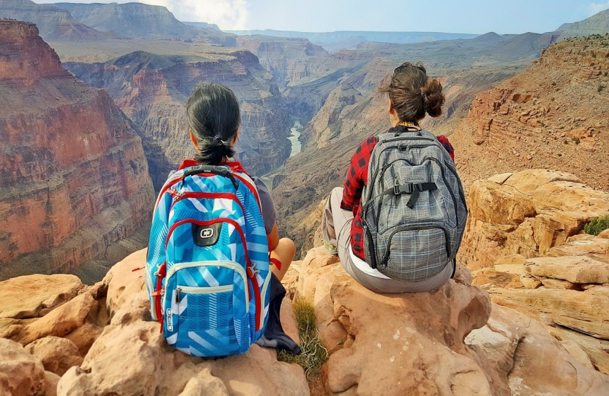 Benefits of travel. Two ladies sitting on the edge of The Grand Canyon.