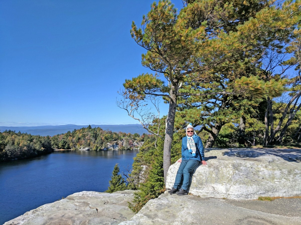 Benefits of travel. A lady resting at Minnewaska State Park Preserve.