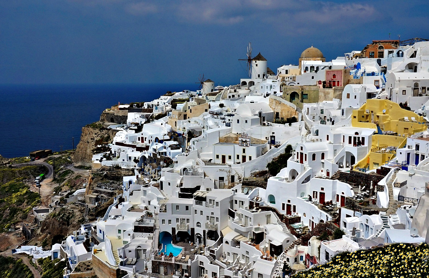 White houses of Oia Santorini with a windmill in a distance.
