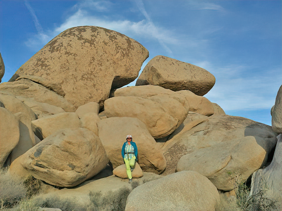 Lady against big boulders in Joshua Tree National Park.
