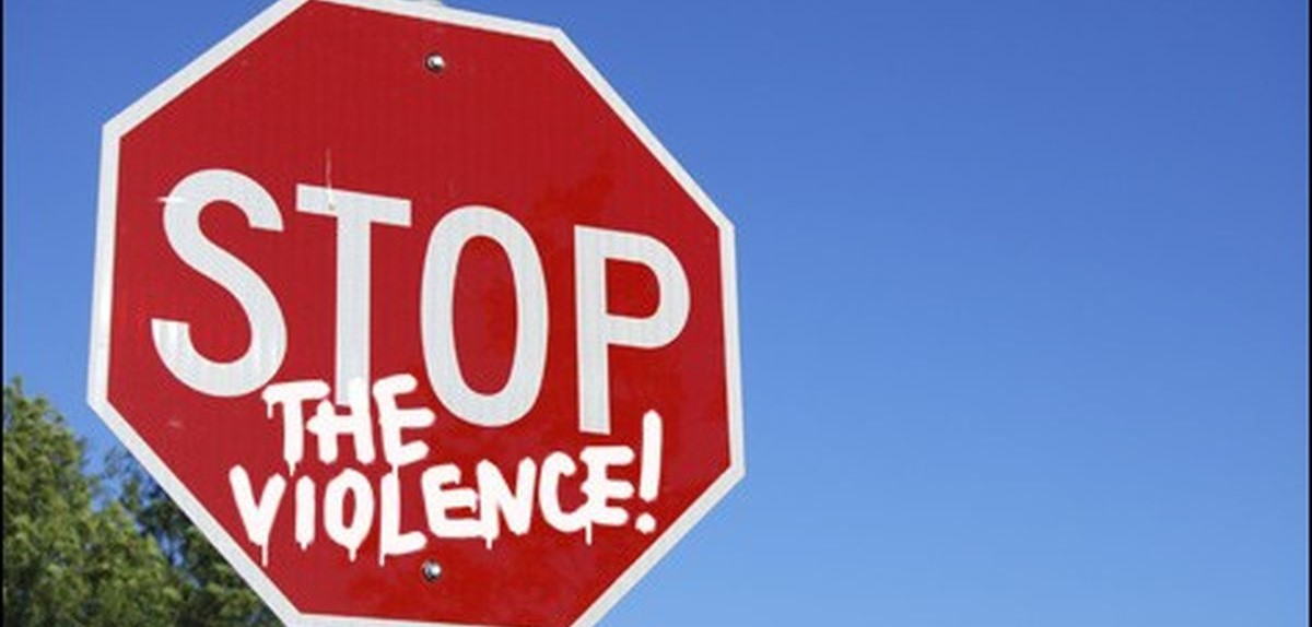 A photo of a stop sign that reads stop the violence