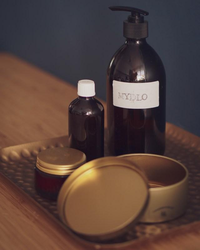 Szklane butelki oraz metalowe pojemniki na kosmetyki
