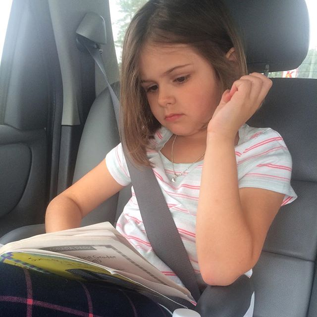 First thing this kid did when getting in the car after school was to open her library book. #Meliamae #lovemygirl #justlikeherdad