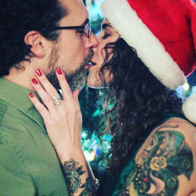 """Just wanted to take a second to say how much I love this woman. My heart, my mirror, your love continues to amaze me and make me feel grateful every day. """"I love you"""" is not enough. I hope we never forget to #kiss like this almost every day. #WCW #LOML #love #ChristmasLights #SantaHat #tattoo"""