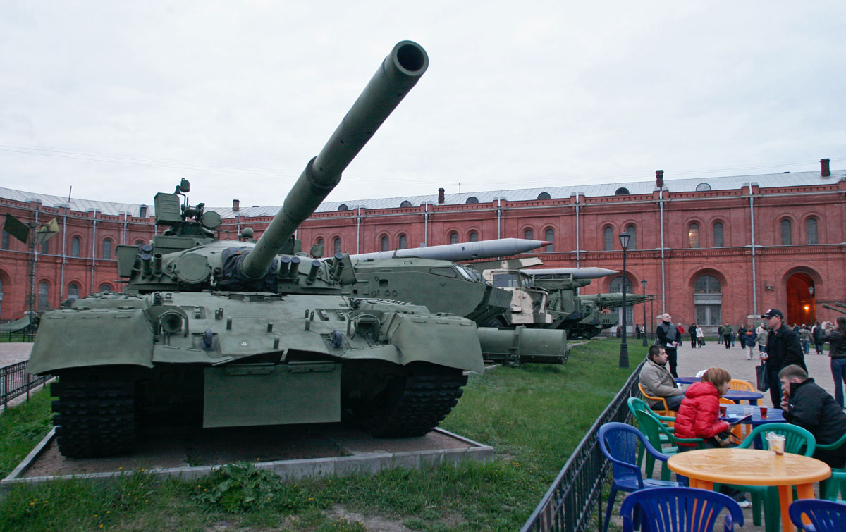 People eat next to a Soviet T-80 tank.
