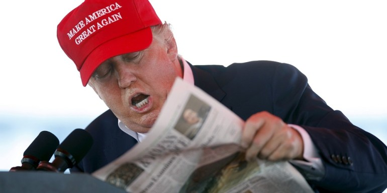 U.S. Republican presidential candidate Donald Trump reads from the Wall Street Journal while speaking at a Trump for President campaign rally at the Jacksonsville Landing in Jacksonville, Florida October 24, 2015.   REUTERS/Daron Dean