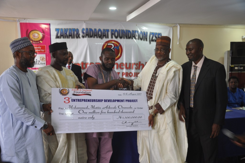 Ambassador Adamu Ibrahim Babangida, presenting a cheque of N1.5 million for coming first during the 3rd Business Plan Competition of Zakat and Sadaqat Foundation, supported on the right by Prince Sulayman Olagunju ED/CEO  ZSF and on the left by Dr Tajudeen Yusuf Chairman Board of Directors ZSF and Imam Abdullahi Shuaib, Executive Secretary/CEO Jaiz Zakat and Waqf Fund.