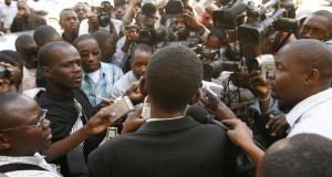 Zimbabwe Electoral Commission lawyer Chikumbirike is met by journalists as he leaves the High Court in the capital Harare
