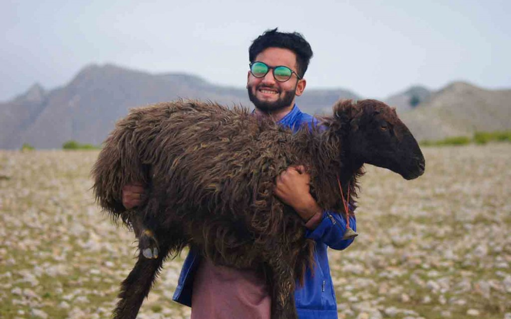 Man holding the sacrificial animal for Eid